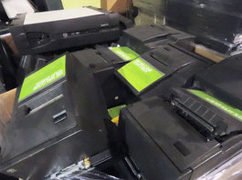 Receipt printers lay in a bin to be recycled/refurbished